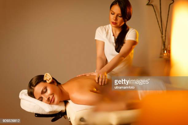 massage therapist doing healing massage. woman enjoying in relaxing massaging at health spa treatment. - massaggio sensuale foto e immagini stock