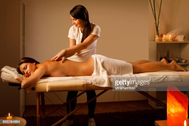 Massage Therapist doing healing massage. Woman enjoying in relaxing massaging at health spa treatment.