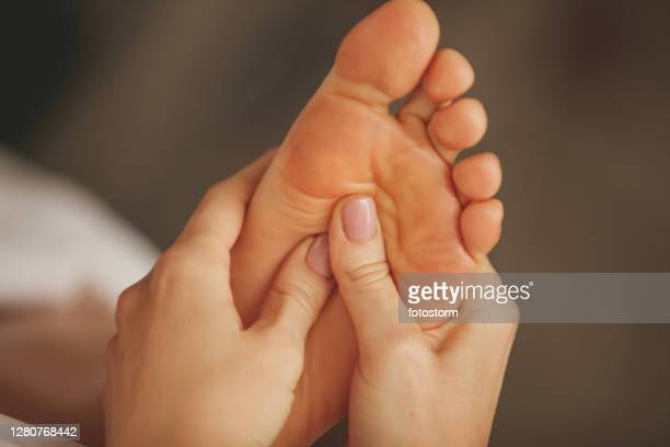 massage therapist giving pain relieving foot massage - foot massage stock pictures, royalty-free photos & images