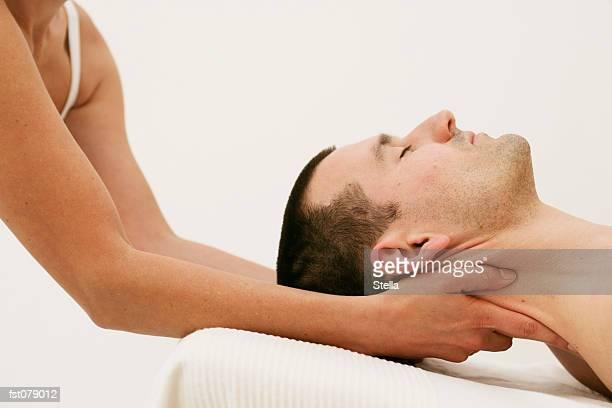 A massage therapist massaging a man?s neck