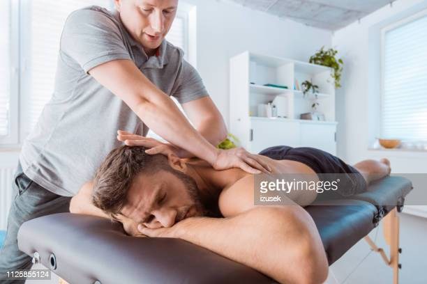 massage therapist massaging back of the young man - massaggi foto e immagini stock