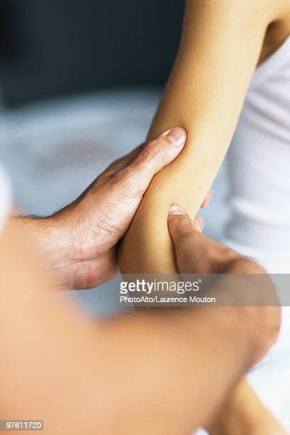 massage therapist massaging patient's arm - osteopath stock photos and pictures
