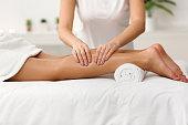 Massage therapist massaging woman calves in spa center