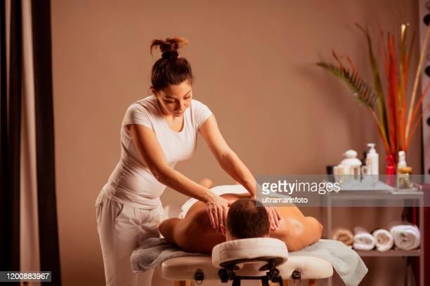 massage therapeut vrouw doet healing massage. man genieten van ontspannen masseren op kuuroord behandeling. - erotische massage stockfoto's en -beelden