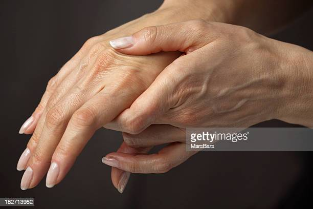 massaging hands in pain - hand cream stock photos and pictures