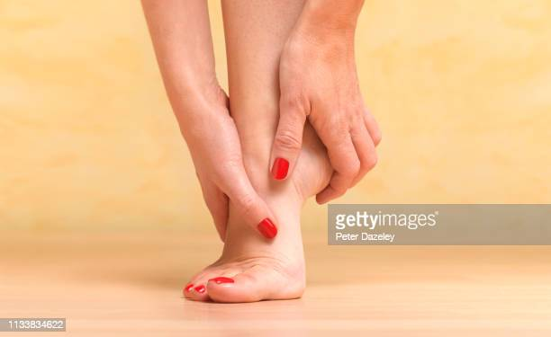 massaging sore foot - human foot stock pictures, royalty-free photos & images