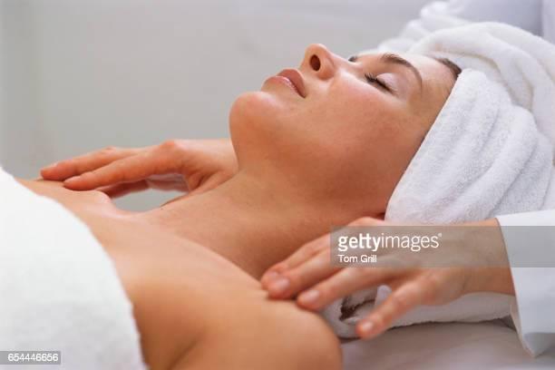 massaging woman's shoulders - massaggio sensuale foto e immagini stock