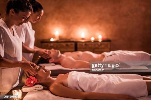 massage jeune couple au spa! - massage couple photos et images de collection