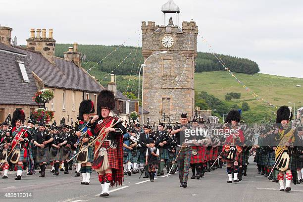 massed pipe bands marching in dufftown, scotland. - highland games stock pictures, royalty-free photos & images