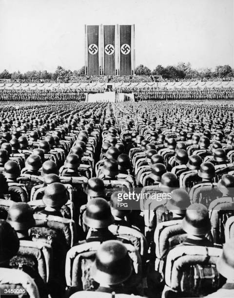 Massed troops stand at attention an dlisten to speeches during a Nazi rally in Nuremberg, Germany, September 1934. Among the speakers at the rally...
