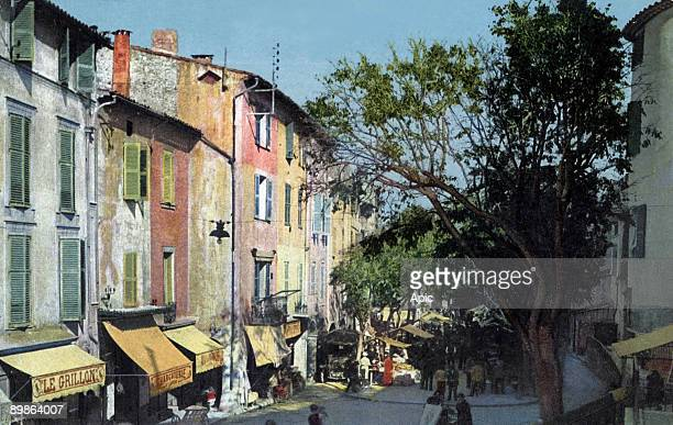 Massena street during market and the Orme gate in Antibes postcard 1938