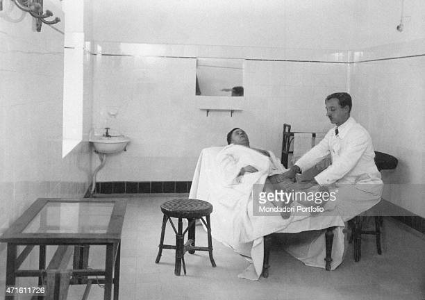 A masseur at the Agnano Spa doing a legs drymassage with talcum powder and vaseline Naples 1920s