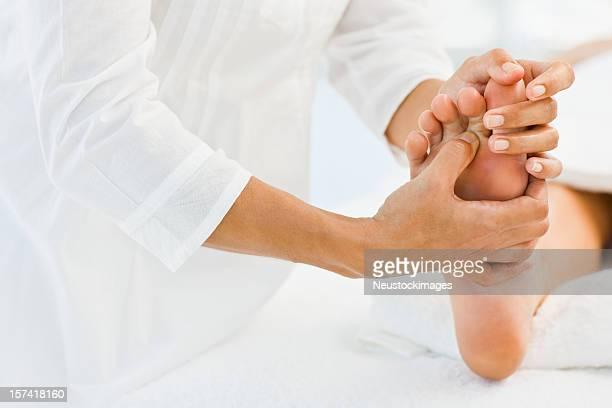 masseur massageando perna humana no spa - foot massage - fotografias e filmes do acervo