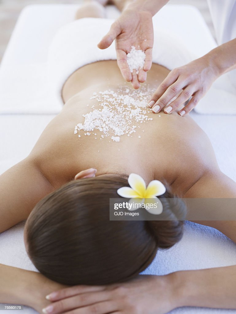 Masseuse applying massage salts to a woman's back : Stock Photo