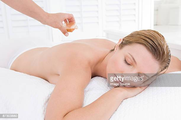 A masseuse applying oil to a womans back