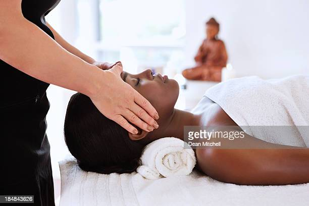 masseuse giving a head massage - massage black woman stock photos and pictures