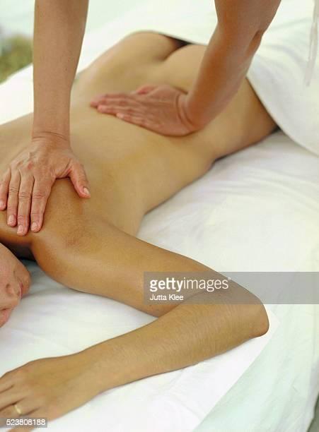 masseuse giving back massage - massaggio sensuale foto e immagini stock