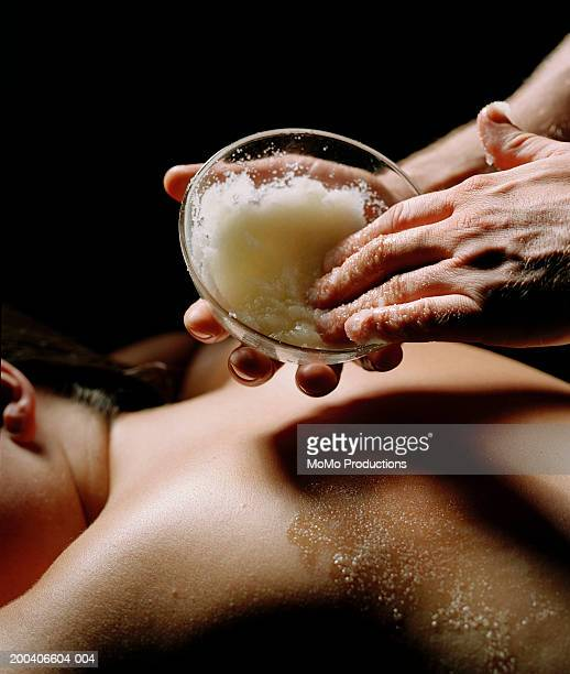 Masseuse giving woman mineral salts treatment, close-up