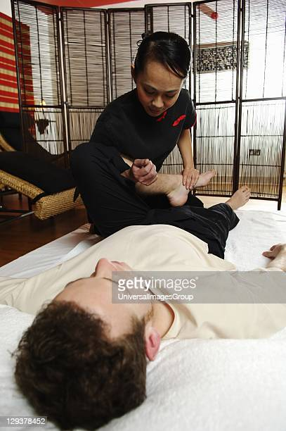 Masseuse stretching her client's legs as part of Thai massage