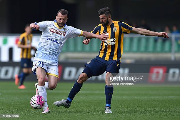 Massimiliano Carlini of Frosinone Calcio is challenged by Eros Pisano of Hellas Verona FC during the Serie A match between Hellas Verona FC and...