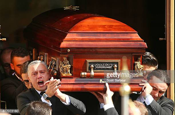 Massimo Acquaro applauds as he and fellow pallbearers carry the coffin from the church after the funeral service for Joseph 'Pino' Acquaro at St...