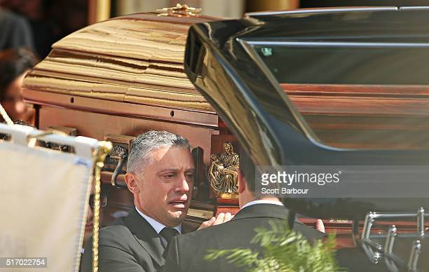 Massimo Acquaro looks on as he and fellow pallbearers carry the coffin from the church after the funeral service for Joseph 'Pino' Acquaro at St...