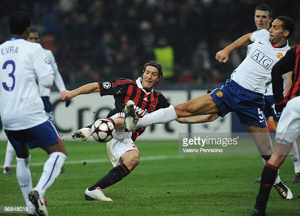 Massimo Ambrosini of AC Milan is challenged by Rio Ferdinand of Manchester United during the UEFA Champions League round of 16 first leg match...