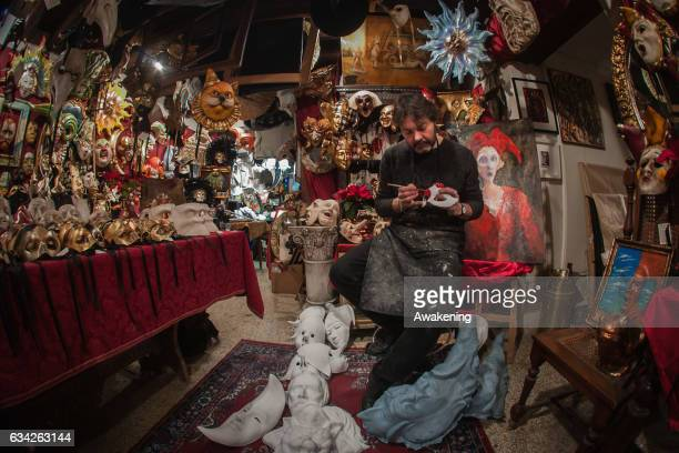 Massimo Boldrin a traditional artisan who specilises in papiermache finishes painting a red mask at La Bottega dei Mascareri which created the masks...