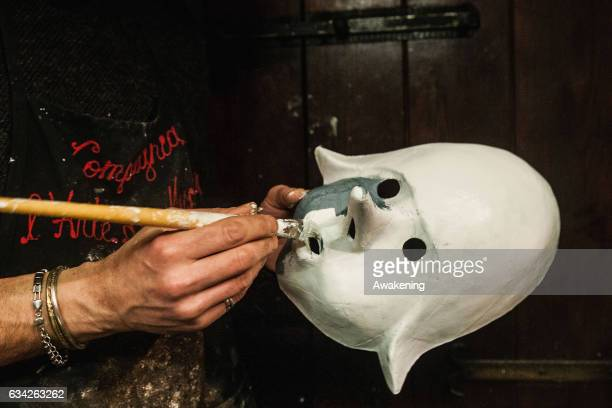 Massimo Boldrin a traditional artisan who specilises in papiermache paints a mask white at La Bottega dei Mascareri which created the masks for...
