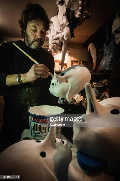 Massimo Boldrin a traditional artisan whospecialises in papiermache finishes painting a mask at La Bottega dei Mascareri which created the masks for...