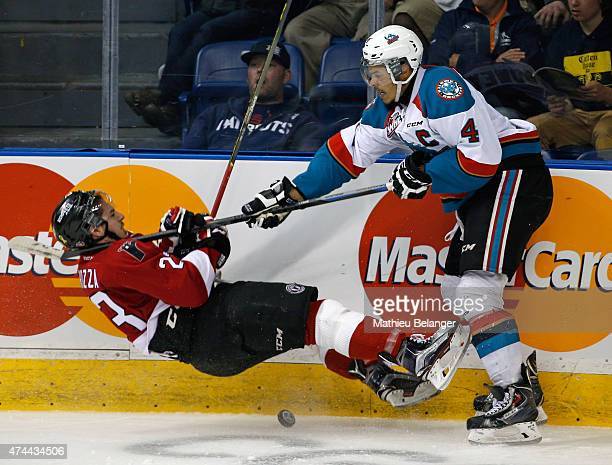 Massimo Carozza of the Quebec Remparts falls on the ice after being hit by Madison Bowey of the Kelowna Rockets during Game One of the 2015 Memorial...