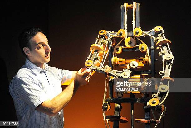 Massimo Ingrosso inspects the complete mechanism of a robot at a Leonardo Da Vinci exhibition titled 'Anatomy to Robots' in Melbourne on October 28 a...
