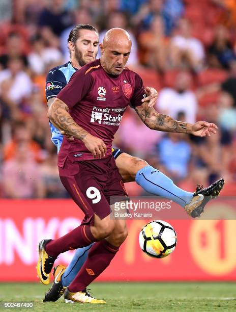 Massimo Maccarone of the Roar is pressured by the defence of Joshua Brillante of Sydney during the round 15 ALeague match between the Brisbane Roar...