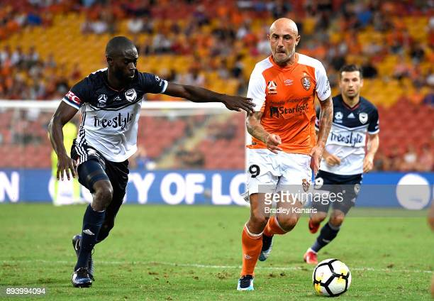 Massimo Maccarone of the Roar takes on the defence during the round 11 ALeague match between the Brisbane Roar and the Melbourne Victory at Suncorp...