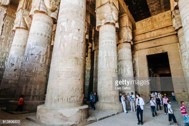 massive columns and visitors at dendera temple - tempelcomplex van dendera stockfoto's en -beelden