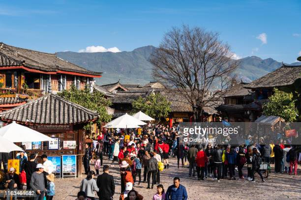 massive crowd of chinese tourism visiting the famous lijiang old town in yunnan - didier marti stock photos and pictures