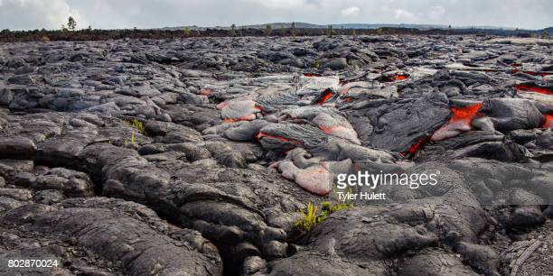massive flow of lava moves across rocky landscape - pele goddess stock pictures, royalty-free photos & images