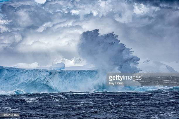 massive iceberg floating in antarctica in a storm - antarctique photos et images de collection
