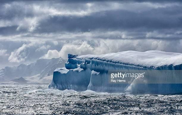 massive iceberg floating in antarctica - antartide foto e immagini stock
