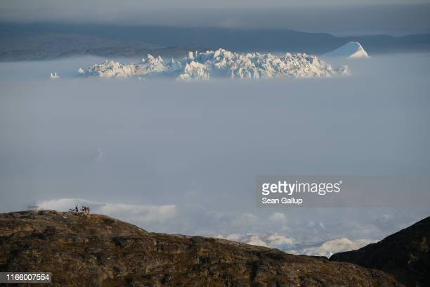 A massive iceberg peeks out from fog in the Ilulissat Icefjord during a week of unseasonably warm weather on August 3 2019 near Ilulissat Greenland...