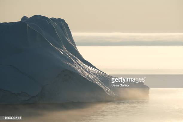 A massive iceberg stands at the mouth of the Ilulissat Icefjord during a week of unseasonably warm weather on August 3 2019 near Ilulissat Greenland...