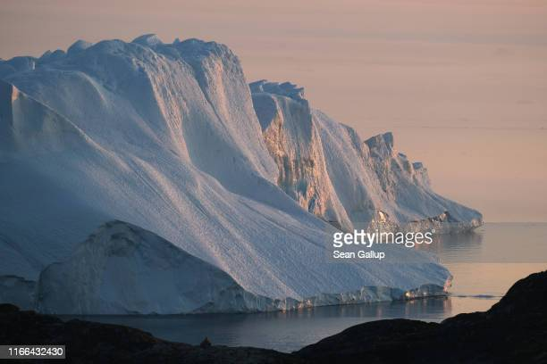 A massive iceberg stands at the mouth of the Ilulissat Icefjord during a week of unseasonably warm weather on August 4 2019 near Ilulissat Greenland...