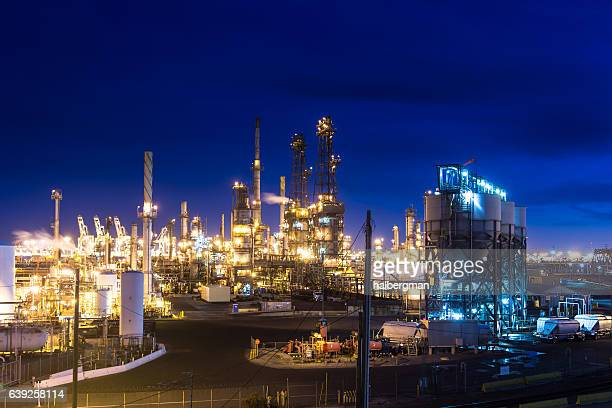 massive oil refinery lit up at night - flare stack stock photos and pictures