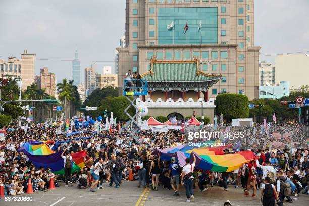 Massive rainbow flags are carried by volunteers and activists through the crowds to mark the start of the annual Taiwan Pride Three different routes...