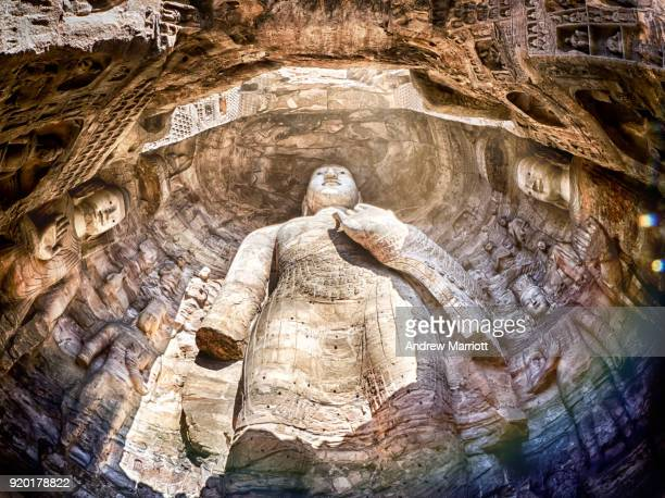 Massive standing Buddha statue in cave full of natural light