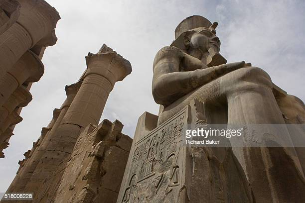 Massive stitting colossus in the Court of Ramesses II at the ancient Egyptian Luxor Temple Nile Valley Egypt The temple was built by Amenhotep III...