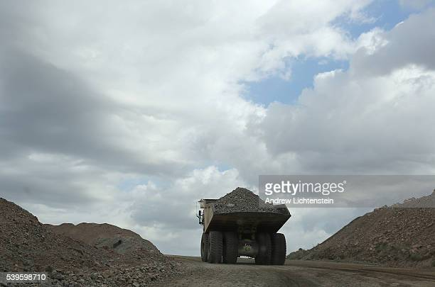 Massive trucks each costing over four million doallars haul crushed rocks around the ginat open pit Ray copper mine in the Sonoran Desert The small...