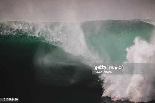 massive wave spiting a huge barrel under the cliffs of moher, ireland - sea stock pictures, royalty-free photos & images