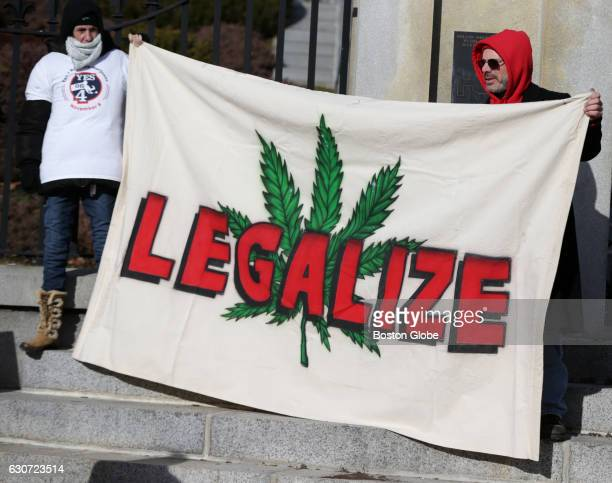 Mass/Normal protesters hold up a banner that says 'legalize' over a cannabis leaf during a Mass/Normal protest at the Massachusetts State House in...