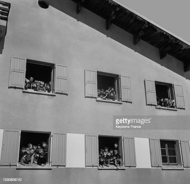 Massés aux fenêtres du chalet collectif les écoliers profitent des sports d'hiver pendant leurs classes de neige en 1967 en France